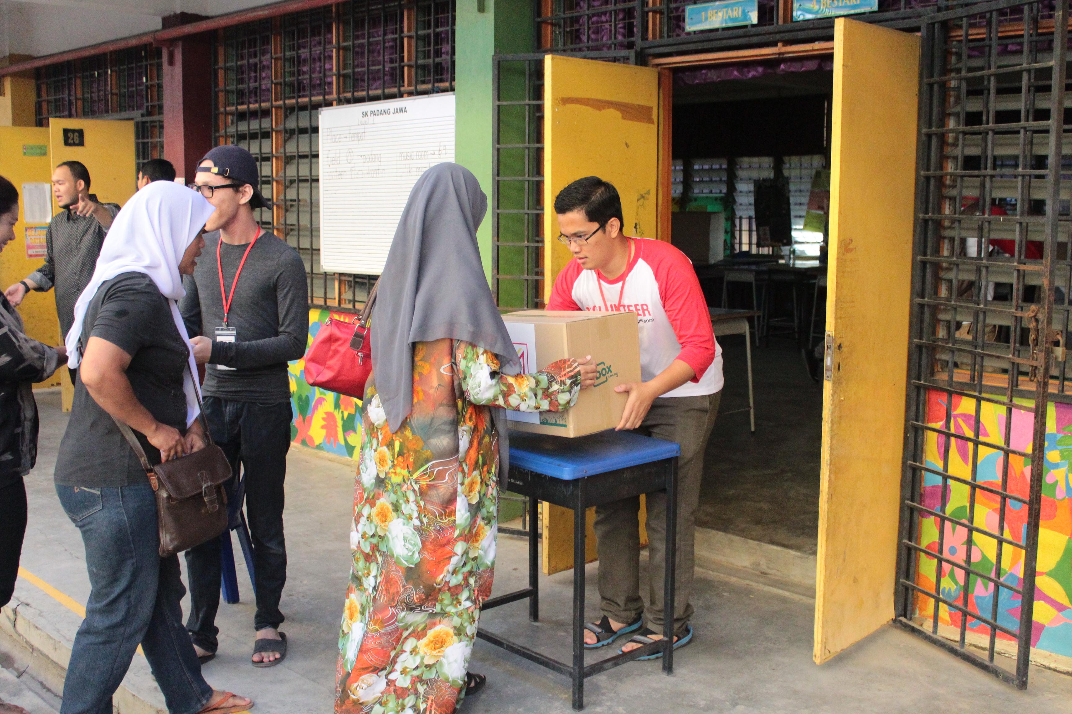 Sukarelawan MVM mengagihkan Kotak bantuan asas kepada keluarga yang memerlukan